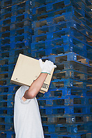 Warehouse Worker Carrying Box past stack of pallets side view