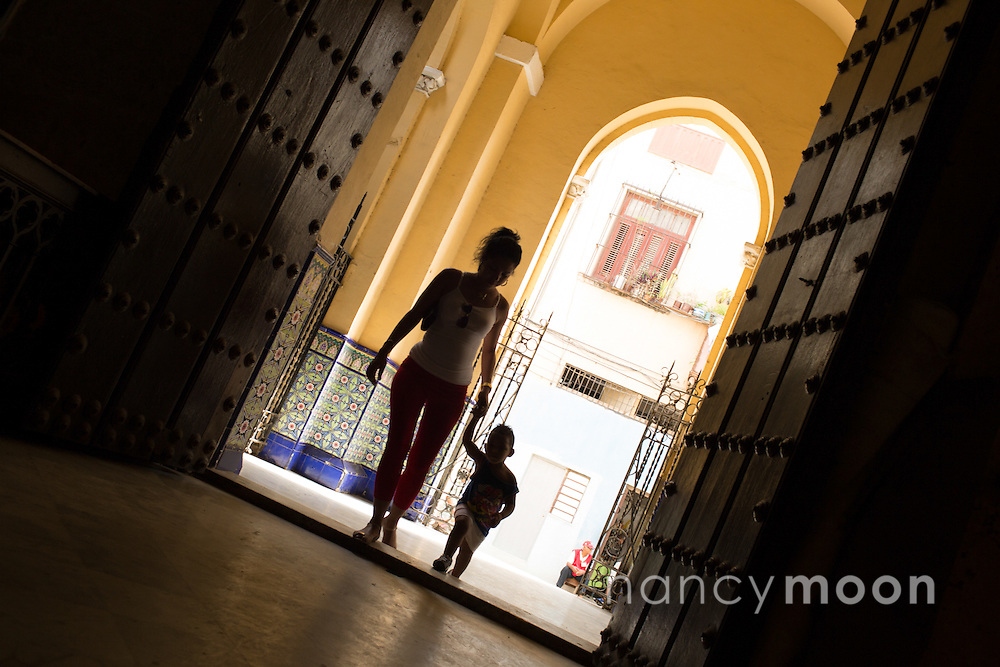 Havana, Cuba church with mother and child entering with the bright sun behind them.<br />