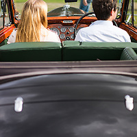 A young adult couple sitting in an old car art a car show in Suffolk