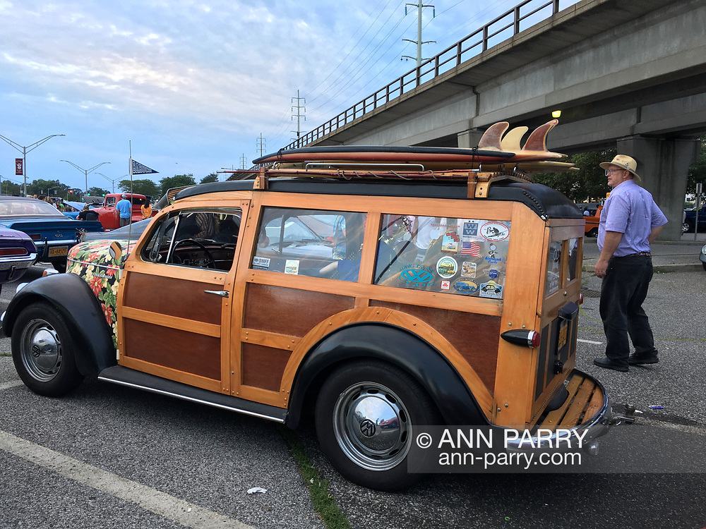 Bellmore, New York, USA. 11th August 2017. At Bellmore Friday Night Car Show, MIKE RADOMSKI, of Valley Stream, is the owner of Wunderbug Woody Volkswagen, with homemade angel hood ornament. Elevated tracks of Bellmore Long Island Rail Road station are seen in background.
