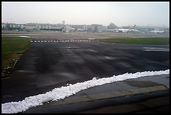 Small amounts of snow on the edge of the runway at Heathrow. Flights were delayed over the weekend due to snow, Monday February 6, 2012. Photo By Andrew Parsons/ i-Images<br /> <br /> File Photo - New runways at Heathrow and Gatwick are among the options that have been short-listed by the Airports Commission for expanding UK airport capacity.<br /> Date filed Tuesday 17th December 2013. Photo By Andrew Parsons/ i-Images.