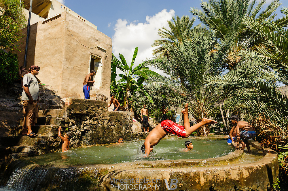 Kids playing and diving in a water basin in misfat, Oman