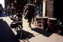 KATHMANDU, NEPAL - OCTOBER 1992 - Sherpas carry heavy loads on their backs through the streets of Kathmandu. (PHOTO © JOCK FISTICK)