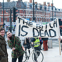 London, UK - 8 April 2013: People hold a sign reading 'The Bitch is Dead' in Brixton during the street party for the death of Margaret Thatcher