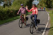 A man and woman wave and smile as they cycle electric bikes along a country lane in Staplehurst, Kent, England, UK.  There are more cyclists part of the group in the background.  (photo by Andrew Aitchison / In pictures via Getty Images)