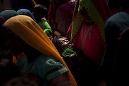 Flood-affected women wait with their children at a roadside camp to be treated at a mobile nutrition centre, on October 4, 2011, in Tando Bago, Pakistan. According to UN reports, hundreds of thousands of children in Pakistan suffer from severe-acute-malnutrition, with 15.1% of children experiencing acute malnutrition. Child malnutrition has breached emergency levels in Pakistan's Sindh province, after monsoon floods devastated the country's poorest region for a second year. Extreme poverty, poor diet and health, exposure to disease, and inadequate sanitation and hygiene annually produce alarming levels of malnutrition amongst children, but the floods have increasingly endangered an already vulnerable population. (Photo by Warrick Page)