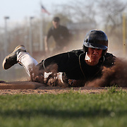 A player slides back to first base creating a cloud of dust during the High School Baseball ball game between Trumbull Golden Eagles and McMahon Senators at Brien McMahon High School. Norwalk, Connecticut. USA. 26th April 2012. Photo Tim Clayton