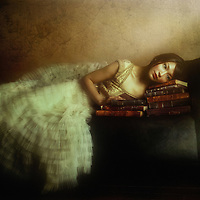 A young Asian woman wearing a long white dress with thoughtful expression resting on old books on a sofa