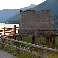 Palafitta, ricostruita, senza pareti sullo sfondo le montagne della Valle di ledro dove i palafitticoli andavano a cacciare