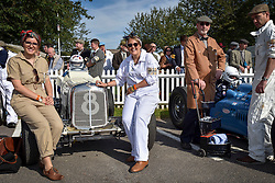 **CAPTION CORRECTION. Picture originally sent with wrong date. Picture was taken TODAY 11/09/2015** © licensed to London News Pictures. 11/09/2015<br /> Goodwood Revival Weekend, Goodwood, West Sussex. UK.<br /> The Goodwood Revival is the world's largest historic motor racing event. Competitors and enthusiasts dress in period fashions recreating the glorious days of the race circuit.<br /> Pictured. Mechanics next to their 1936 ERA.<br /> <br /> Photo credit : Ian Whittaker/LNP