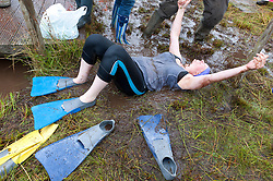 © Licensed to London News Pictures. 30/08/2015. Llanwrtyd Wells, Powys, Wales, UK. Participants are exhausted after the event. World Bogsnorkelling Championships, conceived 30 years ago in a Welsh pub by landlord Gordon Green, are held every August Bank Holiday at Waen Rhydd Bog. Using unconventional swimming strokes, participants swim two lengths of a 55 metre trench cut through a peat bog wearing snorkel and flippers. The world record was broken in 2014 by 33 year old Kirsty Johnson from Lightwater, Surrey, in a time of 1 min 22.56 secs. Photo credit: Graham M. Lawrence/LNP