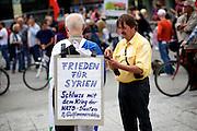 Frankfurt am Main | 30 Aug 2014<br /> <br /> Am Samstag (30.08.2014) demonstrierten &uuml;ber 200 Aktivisten aus dem Umfeld der Partei &quot;Die Linke&quot; und anderen linken und linksradikalen Zusammenh&auml;ngen gegen Krieg und f&uuml;r Frieden. Einige ukrainische Nationalisten und Aktivisten der dubiosen Montagsmahnwache in Frankfurt hatten sich unter die Friedensdemonstranten gemischt.<br /> Hier: Der Aktivist Thomas Occupy (r) spricht mit einem Aktivisten, der ein Plakat mit der Aufschrift &quot;Frieden f&uuml;r Syrien - Schluss mit dem Krieg der Nato-Staaten &amp; Golf-Monarchien&quot; auf dem R&uuml;cken tr&auml;gt.<br /> <br /> &copy;peter-juelich.com<br /> <br /> [No Model Release | No Property Release]