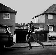 Teenager leaps for a ball in a suburban street, Greenford, London, UK, 1979.