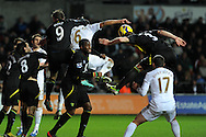 Swansea city's Ashley Williams © is squeezed out by Grant Holt and Steven Whittaker of Norwich city. Barclays Premier league, Swansea city v Norwich city at the Liberty Stadium in Swansea, South Wales on Saturday 8th Dec 2012. pic by Andrew Orchard, Andrew Orchard sports photography,