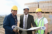 Three construction workers standing on construction site with blueprints