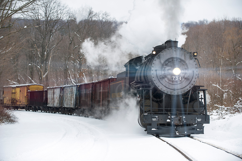 A vintage steam locomotive with bright headlight pulling train in winter snow, pushing a strong white smoke plume into the cold mountain air near Cumberland, Maryland, MD, USA.