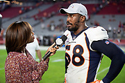 A FOX Sports sideline reporter does a television interview with Denver Broncos linebacker Von Miller (58) after the NFL week 7 regular season football game against the Arizona Cardinals on Thursday, Oct. 18, 2018 in Glendale, Ariz. The Broncos won the game 45-10. (©Paul Anthony Spinelli)