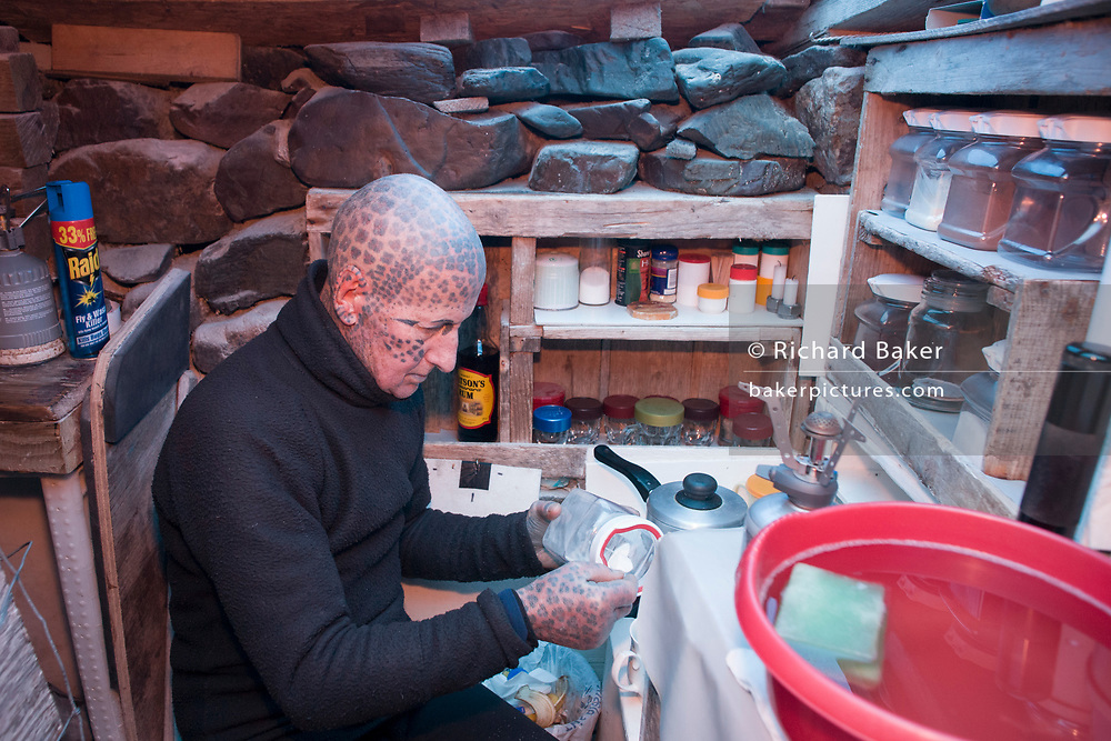 Tattoed hermit Tom Leppard (aka Leopard Man) makes tea in his secret makeshift underground hideaway shelter on Skye, Scotland