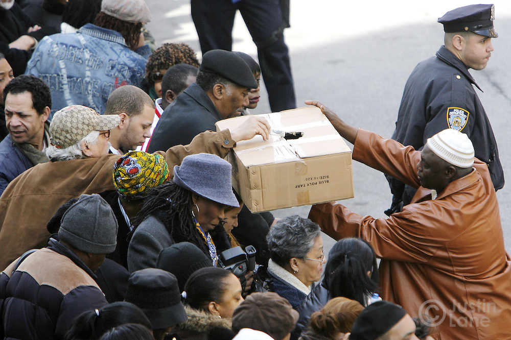 A man collects donations from the crowd during funeral services for the ten people killed in a recent house fire at the Islamic Cultural Center in the Bronx, New York on Monday 12 March 2007. Of the ten people killed in the fire, 9 were children, and all were immigrants from Mali.