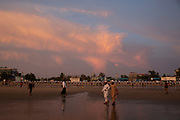 Asian men walk along the sandy Laboni Beach at sunset in Cox Bazar, Chittagong Division, Bangladesh, Asia. A line of sun-beds and umbrellas are further along the beach, with seafront buildings behind.  (photo by Andrew Aitchison / In pictures via Getty Images)