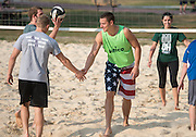 """Mike Hageman, center, and other members of the intramural volleyball teams """"Notorious DIG"""" and """"Delta Sigma Pi"""" shake hands after a game on Sept. 30, 2014, on South Beach. Photo by Lauren Pond"""