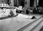 Archbishop elect of Dublin, Desmond Connell, lying prostrate before the altar in the Pro-Cathedral during his ordination ceremony. Connell's nomination for the position by Pope John Paul II, following the death of Archbishop Kevin McNamara in April 1987, surprised many.<br />