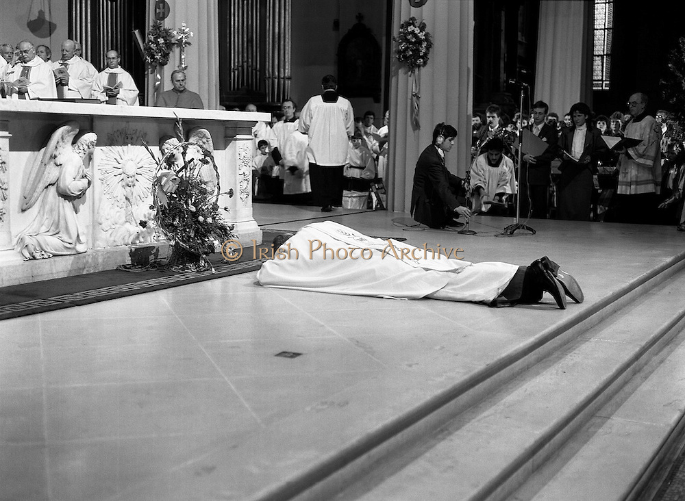 Archbishop elect of Dublin, Desmond Connell, lying prostrate before the altar in the Pro-Cathedral during his ordination ceremony. Connell's nomination for the position by Pope John Paul II, following the death of Archbishop Kevin McNamara in April 1987, surprised many.<br /> 6 March 1988