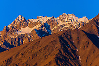 Peaks of the Pamir Mountains (at sunrise) that ring Tashkurgan (means Stone Fortress in Uyghur), at 10,100 feet, along the Karakoram Highway. It was a caravan stop on the Silk Road and all routes of the Silk Road converged here to journey southward to Pakistan. It sits on the borders of both Afghanistan and Tajikistan, and is close to the border of Kyrgyzstan and Pakistan.  The majority population in the town are ethnic Mountain Tajiks. Xinjiang Province, China.