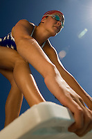 Female swimmer on starting blocks (low angle view)