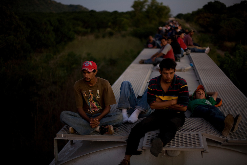 Central American migrants ride atop a freight train carrying cement as they head north in an attempt to enter the US.  Traveling by train has become more dangerous as kidnappings and robberies have risen in recent years with increase drug cartel activity.