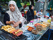 10 JULY 2015 - BANGKOK, THAILAND: A Muslim woman selling grilled meats wait for Muslims to come to Iftar at Haroon Mosque in Bangkok. Iftar is the evening meal when Muslims end their daily Ramadan fast at sunset. Iftar is a communal event at Haroon Mosque and hundreds of people usually attend the meal.     PHOTO BY JACK KURTZ