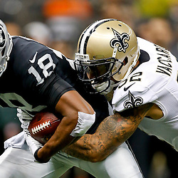 Aug 16, 2013; New Orleans, LA, USA; New Orleans Saints strong safety Kenny Vaccaro (32) tackles Oakland Raiders wide receiver Andre Holmes (18) during the second half of a preseason game at the Mercedes-Benz Superdome. The Saints defeated the Raiders 28-20. Mandatory Credit: Derick E. Hingle-USA TODAY Sports