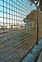 Le Ferrovie del Sud Est nascono in Puglia, nell'ottobre del 1931. A questà nuova società veniva dato in concessione l'insieme delle reti ferroviarie precedentemente gestite da diversi organismi (Società per le Ferrovie Salentine, Società per le Ferrovie Sussidiate, Ferrovie dello Stato)..Le aree pugliesi attraversate dalla società ferroviaria sono l'area barese, la fascia Taranto-Brindisi e l'area leccese-salentina, collegando fra loro i capoluoghi di Bari, Taranto e Lecce, nonché oltre 130 comuni delle province meridionali..Il reportage fotografico sulle Ferrovie Sud Est intende testimoniare l'evoluzione tecnologica che, durante gli anni, ha modificato e migliorato il servizio ferroviario e la convivenza del progresso con tracce del passato, attraverso un viaggio tra le stazioni e i depositi..Grata di recinzione della stazione di Mungivacca.