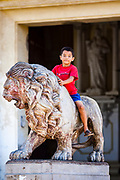 11 JANUARY 2007 - LEON, NICARAGUA: A boy on the lions in front of the cathedral in Leon, Nicaragua, took over 113 years to build. Construction started in 1747. Ruben Dario, Nicaragua's most famous poet, is buried beneath the cathedral. Leon was established in 1524 and was the capitol of what is now Nicaragua for more than 200 years. It was heavily damaged during the Sandanista war against the Somoza regime and it still one of the most liberal cities in Nicaragua.  Photo by Jack Kurtz