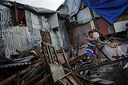 A woman clears debris from her front yard in Yolonda Village. Nearly six months after typhoon Haiyan devastated the area, the hardest hit coastal neighbourhoods are still far from rebuilt.