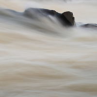 Abstract of the silt-ladden Potomac river water flowing past boulders just above the Great Falls in late January, Great Falls National Park, Great Falls, Virginia