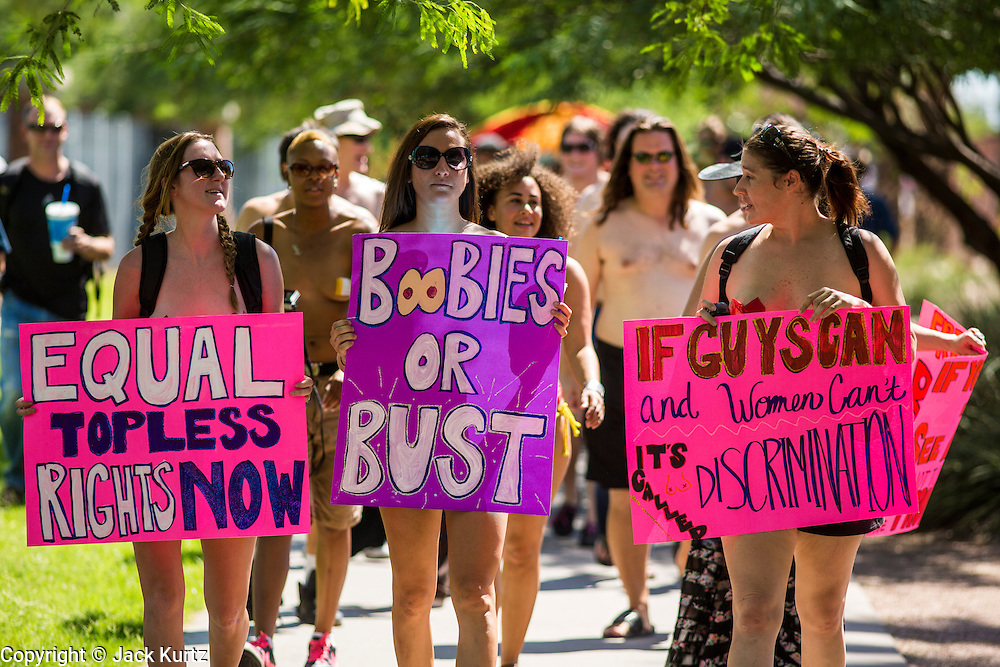 26 MARCH 2012 - PHOENIX, AZ:  JENNA DUFFY, left, MEGAN ERBE and KELLY CAYE lead a march of topless women and men in Phoenix. About 40 people marched through central Phoenix Sunday to call for a constitutional amendment to give women the same right to go shirtless in public that men have. The Phoenix demonstration was a part of a national Topless Day of Protest. Phoenix prohibits women from going topless in public so protesters, women and men, covered their nipples and areolas with tape. The men did it to show solidarity with the women marchers.   PHOTO BY JACK KURTZ
