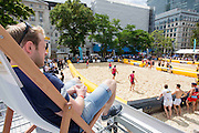UNITED KINGDOM, London: 31 July 2015 A rugby fan enjoys the sun and the view as a game of Beach Rugby gets underway in the heart of London this afternoon at Finsbury Square. The five-a-side rugby tournament imported 240 tonnes of sand for the event, which sees more than 300 rugby players come together and raise money for Help for Heroes. Rick Findler / Story Picture Agency.
