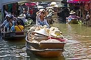 Hat seller in the Damnern Saduak floating market, Bankok, Thailand
