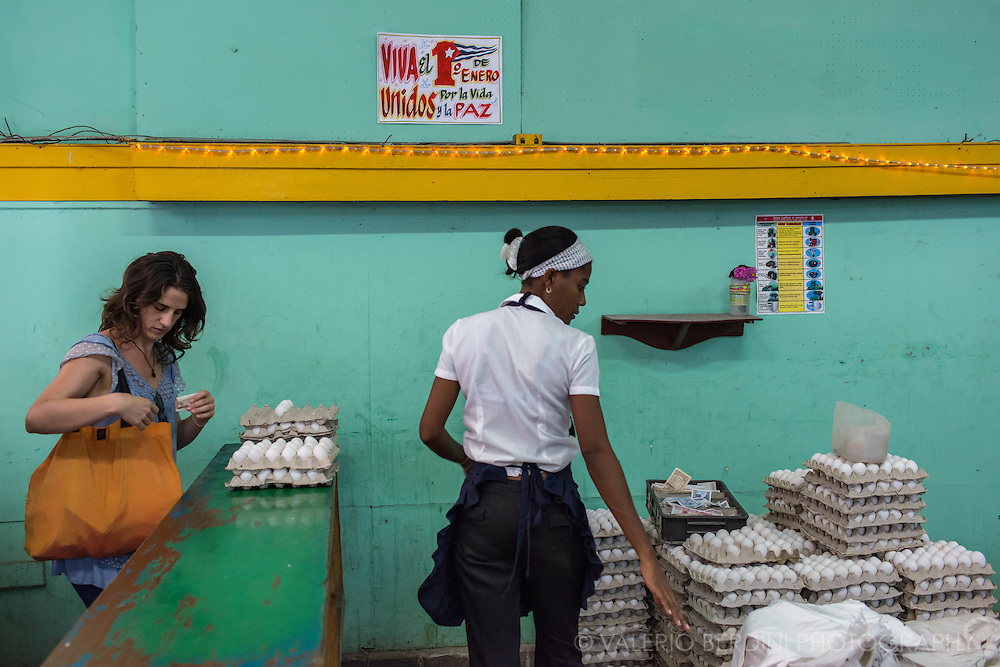 A woman getting her ration of eggs at a local shop (Local Bodega) in Havana. Basic food in Cuba is rationed, every Cuban has right to get 5 eggs a month showing a supplies booklet (Libreta de Abastecimiento). Havana. Cuba, 2015.