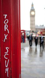 (c) London News Pictures. 10.12.2010. A famous red London phone box stands graffitied in Parliament Square. The clean-up operation in Westminster following last night's student demonstration. Picture credit should read: Brian Duckett/London News Pictures