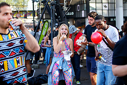 © Licensed to London News Pictures. 29/08/2016. London, UK. Revellers drink, eat and consume legal high drugs on  the second day of Notting Hill Carnival in west London, Monday 29 August 2016. Photo credit: Tolga Akmen/LNP