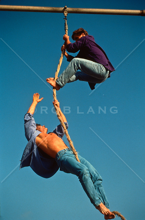 Two men climbing a rope in California