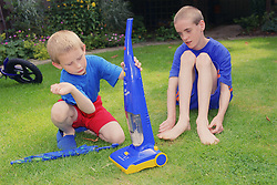 Two brothers with autism playing in garden with toy Hoover,