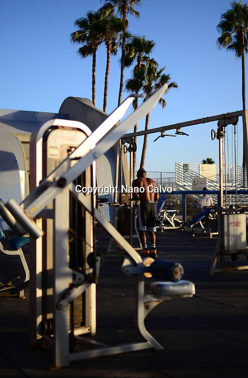 Man training at outdoors gym on Venice Beach, California.