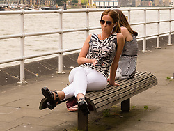 © Licensed to London News Pictures. 24/06/2014. London, UK. A woman listens to music on a bench next to the River Thames in Butlers Wharf during the hot weather in London at lunchtime today. Photo credit : Vickie Flores/LNP