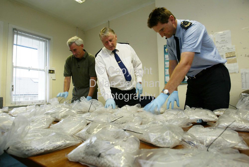 25/9/2003.Irish Independent News.From left  Detective Garda Dermot Lynch, Superintendent Dick Roche and Sargent Kevin Bowen of Clonmel Gardai pictured with the 150,000 ecstacy tablets worth a minimum of EUR1.5m at Clonmel Garda station yesterday evening..Picture Dylan Vaughan