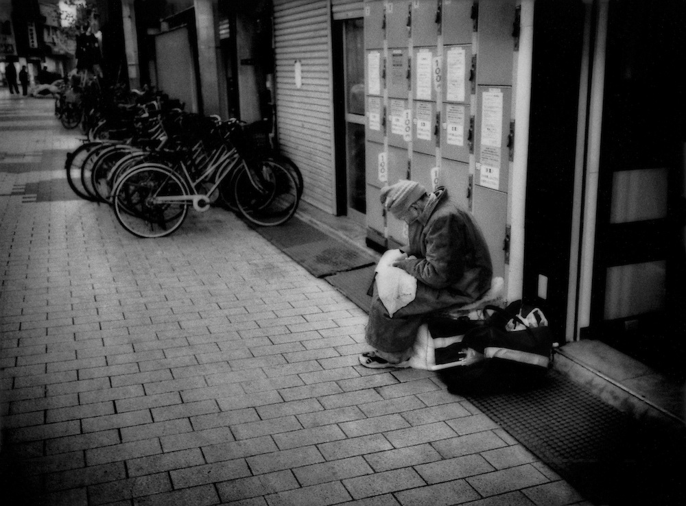 """Homeless on streets / Elderly man huddles with his possessions beside coin lockers, another anonymous senior who has fallen through the cracks, Tokyo, Japan  When he dies, who will inform his family, if he has any, to record the death on their family registry (""""koseki tohon"""").  Will he one day become another 150+ year old still registered as alive?"""