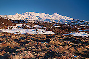 snow and rock lit up by the evening sun in this mountain sunset blue sky photo at mt ruaphehu, tongariro national park, new zealand