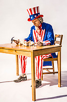 A sad Uncle Sam sitting over a broken piggy bank holding a hammer. Conceptual shot for treasury, deficits, bank, savings, tax revenues.
